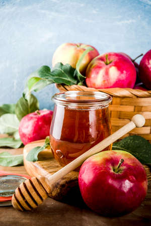 Jewish holiday Rosh Hashanah or apple feast day concept, with red apples, apple leaves and honey in jar, light blue and wooden background copy space