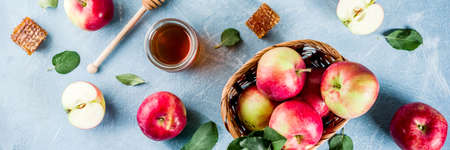 Jewish holiday Rosh Hashanah or apple feast day concept, with red apples, apple leaves and honey in jar, light blue background copy space above banner Stock Photo