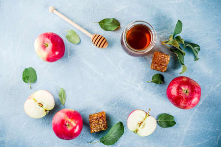 Jewish holiday Rosh Hashanah or apple feast day concept, with red apples, apple leaves and honey in jar, light blue background copy space above frame