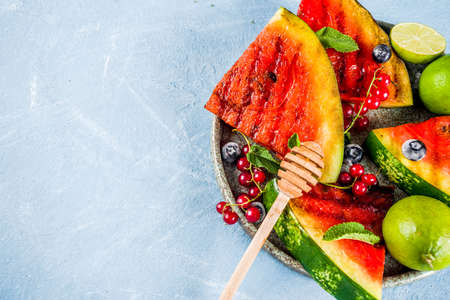 Summer bbq concept, grilled watermelon with berries, mint, lime and honey, light blue background copy space above