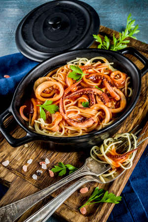 Italian cuisine, Calamari Fra Diavolo, spaghetti pasta marinara with seafood, light blue background copy space top view Stockfoto