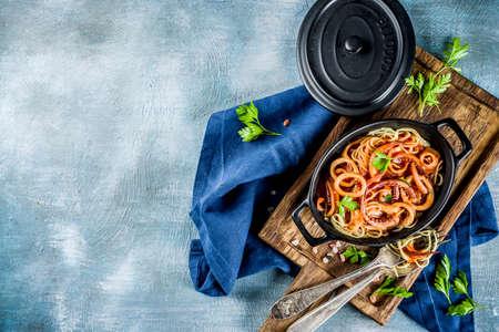 Italian cuisine, Calamari Fra Diavolo, spaghetti pasta marinara with seafood, light blue background copy space top view Stock Photo