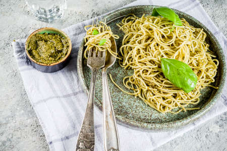 Spaghetti pasta with pesto and fresh basil leaves, grey stone background copy space Stockfoto