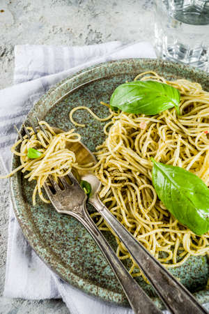 Spaghetti pasta with pesto and fresh basil leaves, grey stone background copy space Stock Photo