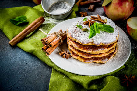 Sweet and spicy autumn apple pancakes, with anise, cinnamon and sugar, dark blue background copy space