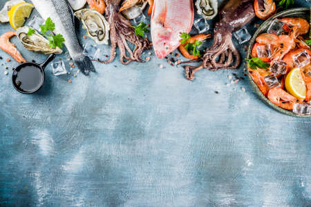 Fresh raw seafood squid shrimp oyster mussels fish with spices of herbs lemon on a light blue background copy space top view