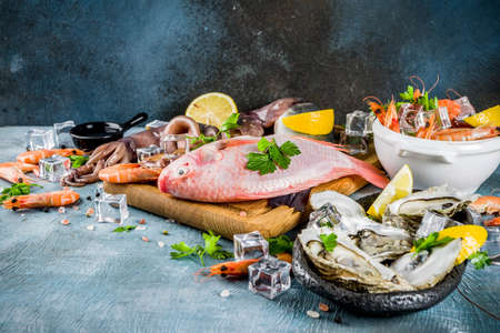 Fresh raw seafood squid shrimp oyster mussels fish with spices of herbs lemon on a light blue background copy space