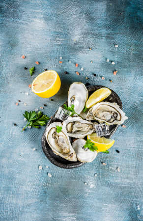 Fresh raw seafood, oysters with lemon and ice on a light blue background