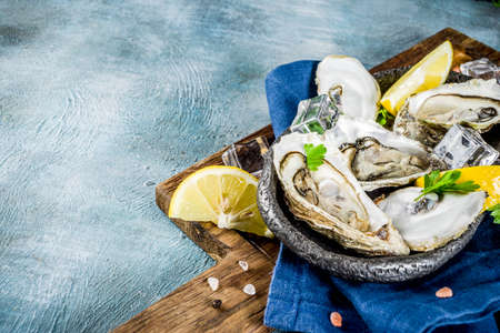 Fresh raw seafood, oysters with lemon and ice on a light blue background 版權商用圖片 - 105043859