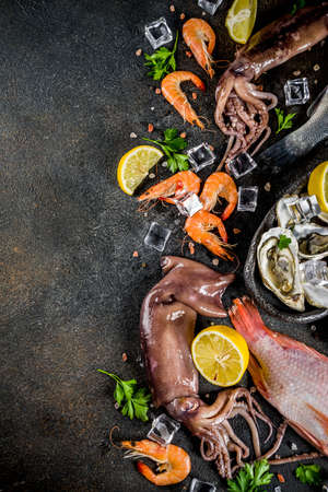 Fresh raw seafood squid shrimp oyster mussels fish with spices of herbs lemon on dark rusty background copy space top view