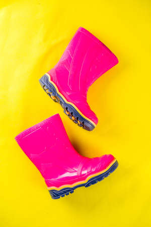 Autumn kids cloth concept, bright pink rubber boots for rain, top view