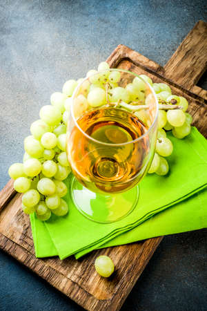 White wine glass with a branch of grapes, on a marble white table, copy space