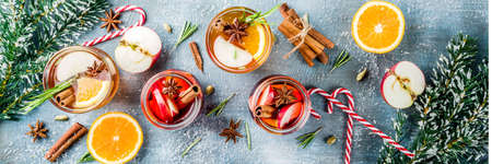 Traditional winter drinks, white and red mulled wine cocktail,  with white and red wine, spices, apple, orange. On a light blue table, banner Stockfoto