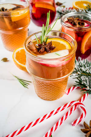 Traditional winter drinks, white and red mulled wine cocktail,  with white and red wine, spices, apple, orange. On white marble background copy space Stockfoto
