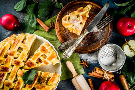 Traditional autumn baking, homemade apple pie with cinnamon, dark blue background with rolling roll, sugar powder, fresh apples, spices, copy space top view Stock fotó