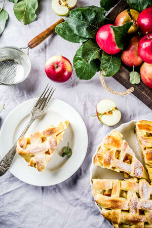 Autumn traditional baked pastry, Sweet homemade apple pie with fresh apples on light linen cloth background, copy space
