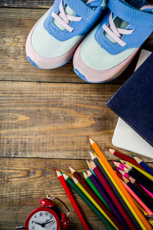 Back to school concept with kids sneakers, books, color pencils and alarm clock, wooden desk background top view copy space