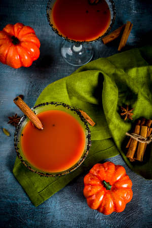 Autumn spicy pumpkin martini with cinnamon, anise stars and black sesame decoration, dark blue background copy space