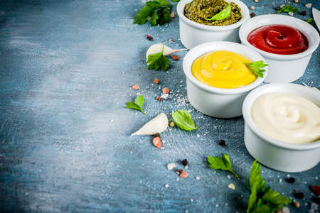 Set of four classic sauces - ketchup, mayonnaise, mustard, pesto - with herbs and spices. Blue concrete background top view copy space Stock Photo