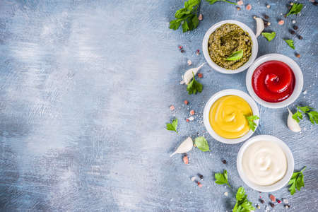 Set of four classic sauces - ketchup, mayonnaise, mustard, pesto - with herbs and spices. Blue concrete background top view copy space Banco de Imagens