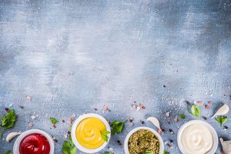 Set of four classic sauces - ketchup, mayonnaise, mustard, pesto - with herbs and spices. Blue concrete background top view copy space Stock fotó