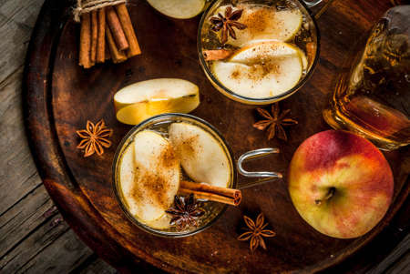 Autumn and winter drinks. Traditional home-made apple cider, cocktail of cider with aromatic spices - cinnamon and anise. On an old wooden rustic table, on a tray. Copy space top view Standard-Bild