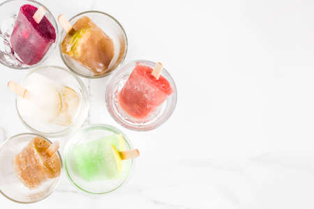 Summer party food ideas, frozen boozy alcohol cocktails - Prosecco, Vodka lime mojito, Champagne, Bellini, Margarita, Negroni etc white marble table copy space