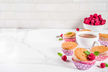 Sweet summer dessert, homemade baked muffin with raspberry jam, served with tea, fresh raspberries and mint. On a white marble table, copy space 写真素材
