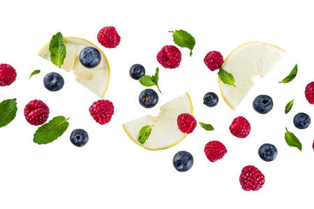 Creative layout, background, with fresh berries, simple pattern on white background. Raspberry, blueberry, mint leaves, slices of lemon.