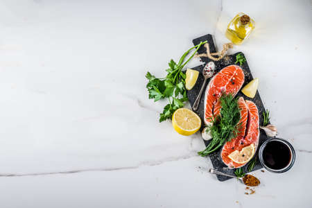 Raw salmon fish steaks with lemon, herbs, olive oil, ready for grill, slate cutting board, white marble background copy space above Stock Photo