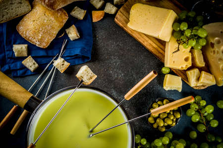 Gourmet Swiss fondue in traditional fondue pot, with forks, various cheeses, olives, bread and grape, dark blue background copy space Banque d'images - 105441140