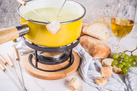 Gourmet Swiss fondue in traditional fondue pot, with forks, various cheeses, olives, bread and grape, white marble background copy space Banque d'images - 105441149