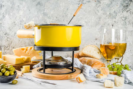 Gourmet Swiss fondue in traditional fondue pot, with forks, various cheeses, olives, bread and grape, white marble background copy space Banque d'images - 105441147