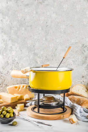 Gourmet Swiss fondue in traditional fondue pot, with forks, various cheeses, olives, bread and grape, white marble background copy space Фото со стока