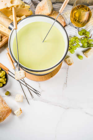 Gourmet Swiss fondue in traditional fondue pot, with forks, various cheeses, olives, bread and grape, white marble background copy space Stock Photo
