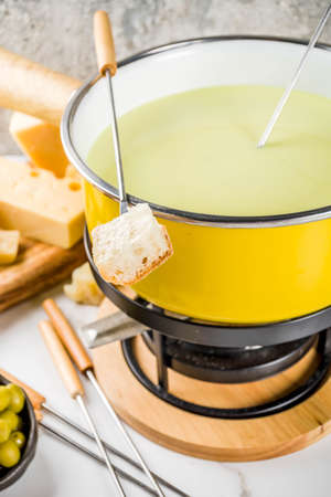 Gourmet Swiss fondue in traditional fondue pot, with forks, various cheeses, olives, bread and grape, white marble background copy space Banque d'images - 105443254