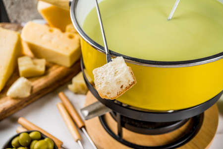 Gourmet Swiss fondue in traditional fondue pot, with forks, various cheeses, olives, bread and grape, white marble background copy space Banque d'images - 105443253