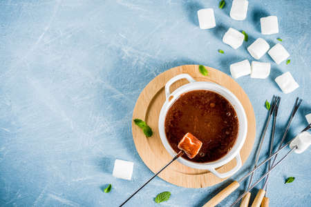Chocolate fondue with marshmallow, winter party food, light blue background copy space Imagens
