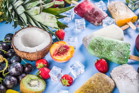 Tropical ice cream popsicles with chia seeds and fruit juices - pineapple, orange, mango, banana, kiwi, coconut, grapes, peach, strawberry, copy space