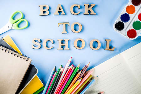 Back to school background with accessories for the schoolroom - paints, pencils, notebooks, books, scissors, chalk, markers, blue background, above copy space