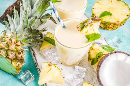 Refreshing summer drink, homemade pina colada cocktail, on a light blue background, with pieces of pineapple, coconut, ice and mint leaves, copy space