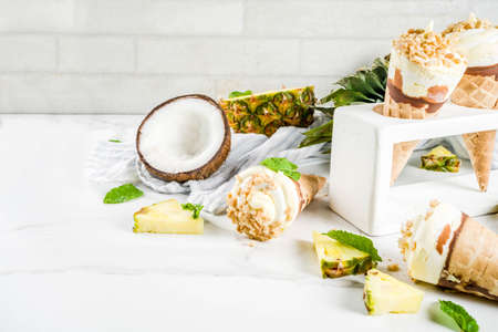 Tropical fruit homemade ice cream, with pineapple and coconut, waffle crumbs, on a white marble table, copy space Stock Photo