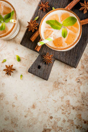 Traditional Indian drink is iced tea or chai masala, with ice cubes from chai, milk and mint leaves. With striped straws, on a wooden board. On light beige stone table. Copy space top view