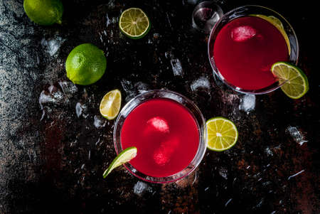 Red cosmopolitan cocktail with lime in martini glass, on dark rusty background copy space top view