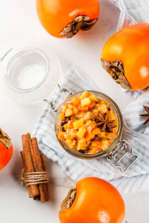 Traditional indian food recipes, Persimmon fruit Chutney with cinnamon and anise stars, white marble background copy space top view