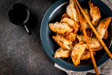 Fried asian dumplings Gyoza  on dark plate, served with chopsticks and soy sauce, dark background, copy space 写真素材