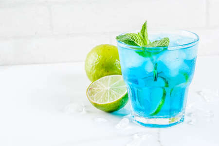 Colorful summer beverage, iced blue alcohol cocktail drink with lime and mint, white marble background copy space