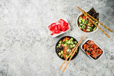 Asian trendy food, sushi poke bowl with cucumber, salmon, avocado, Black and White Sesame Seeds