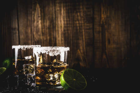 Two tequila shot glasses on dark background, with ice cubes, salt and limes copy space