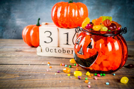 Halloween celebration concept with pumpkin decoration, candy, jack o lantern cup and old retro styled wooden calendar, blue and wooden background, copy space